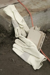 a pair of worker's gloves and suggestion of building materials