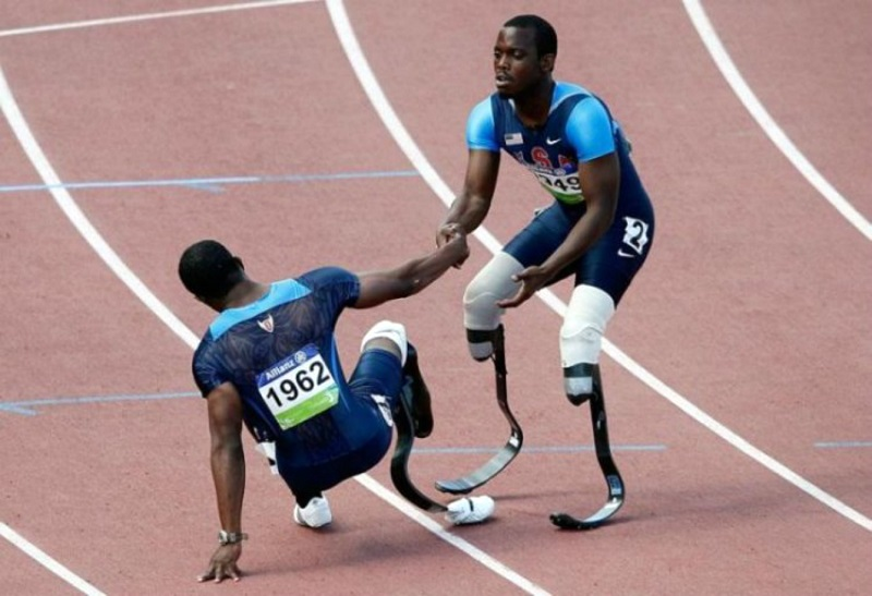An athlete with artificial limbs helping another athlete with artificial limbs